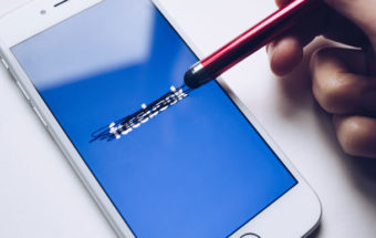 "Hand using a stylus to cross out the word ""facebook"""