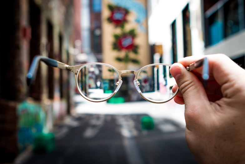 A hand holding a pair of glasses in the center of a street, vision concept